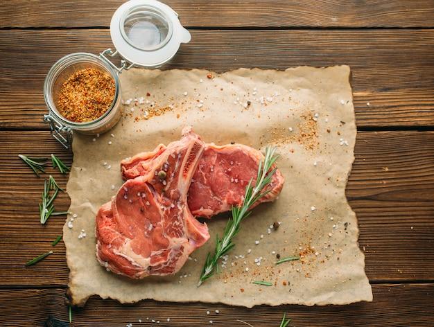 Сырое мясо в приправах на деревянном столе