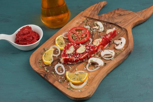 Pezzo di carne cruda con verdure sul tavolo blu.