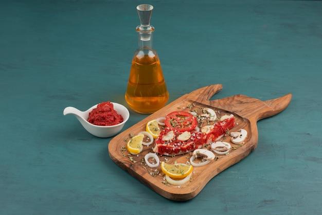 O 기름과 토마토 페이스트 옆에 파란색 테이블에 야채와 함께 생 쌀된 고기 조각.