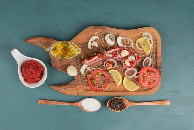 油とトマトペーストの隣の青いテーブルに野菜が入った未調理の肉片。