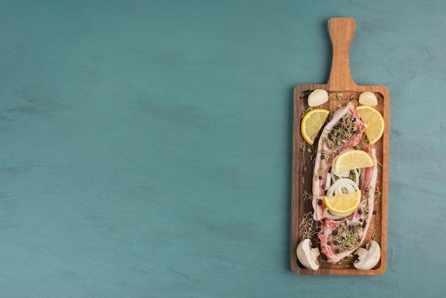 블루 테이블에 야채와 함께 생 쌀된 고기 조각입니다.