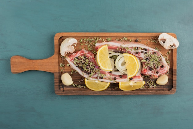 목 판에 야채와 함께 생 쌀된 고기 조각입니다.