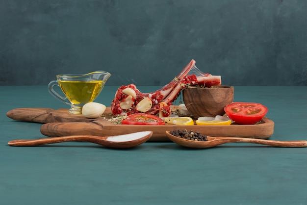 青いテーブルに野菜、油、スパイスを入れた未調理の肉片。