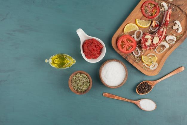 블루 테이블에 야채, 기름, 향신료와 생 쌀된 고기 조각.