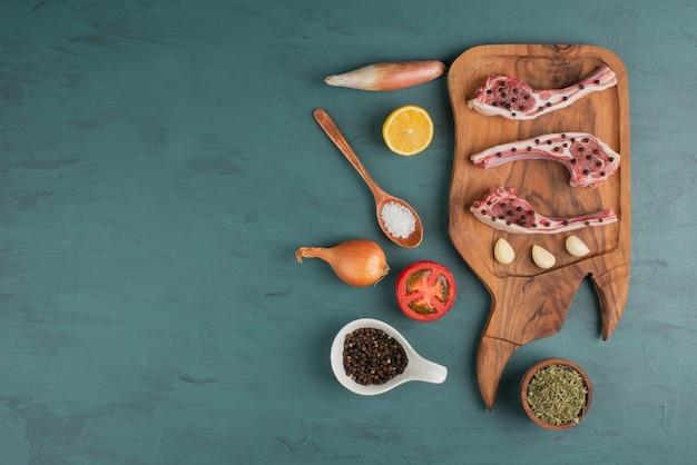 Pezzi di carne cruda con verdure, olio e spezie sul tavolo blu.