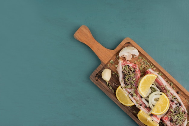 Pezzi di carne cruda su tavola di legno con fette di limone.