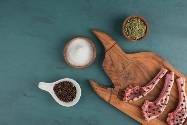 Pezzi di carne cruda su tavola di legno con sale e spezie.
