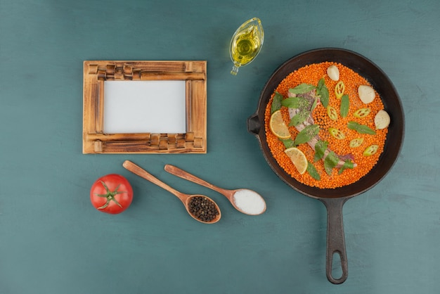 Uncooked meat with red lentil, pepper slices, garlic and spinach in black pan with picture frame and oil.