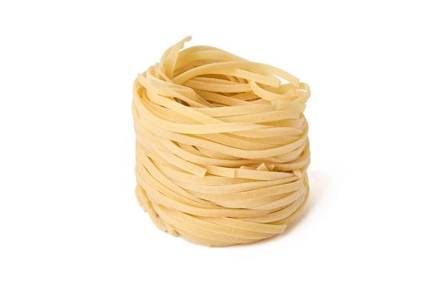 Uncooked nest of fettuccine pasta isolated on white background