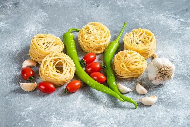 Spaghetti crudi nido con verdure su uno sfondo di marmo
