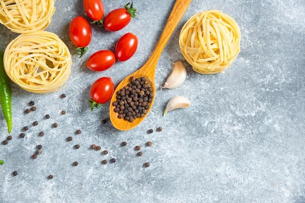 大理石の背景に野菜と未調理の巣スパゲッティ