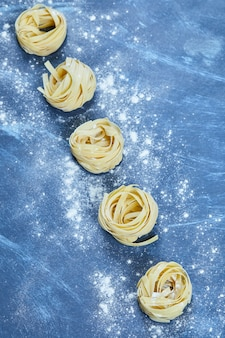 Uncooked nests of tagliatelle pasta isolated.