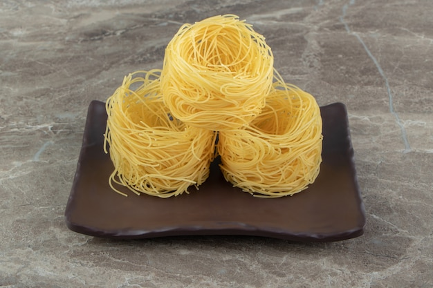 Uncooked noodle nests on dark plate