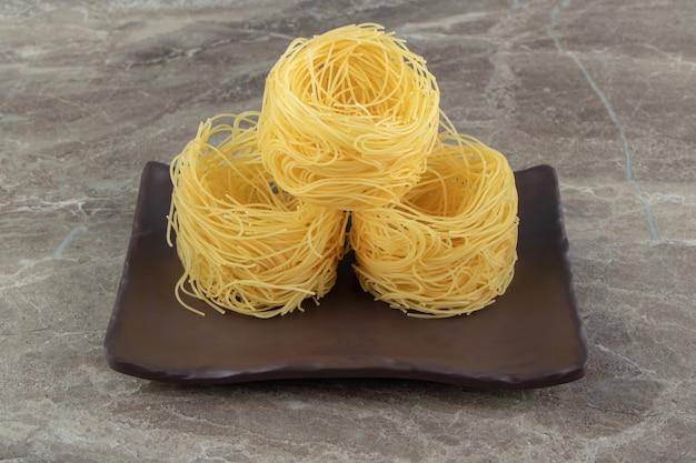 暗いプレート上の未調理の麺の巣