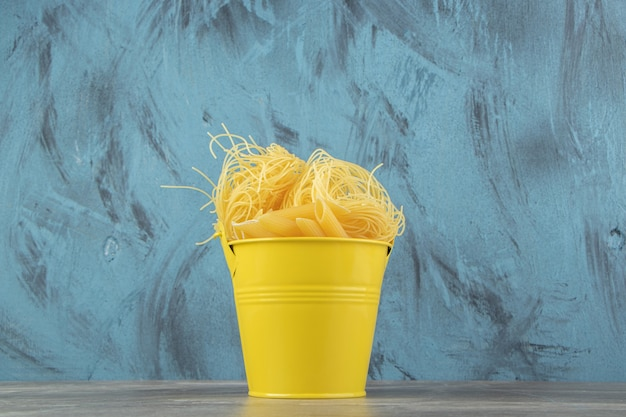Uncooked noodle nests and penne in yellow bucket