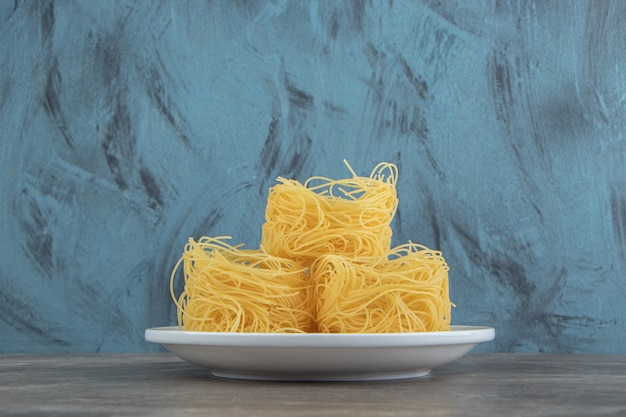 Uncooked noodle nests on white plate
