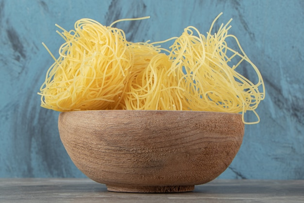 Uncooked noodle nests in wooden bowl