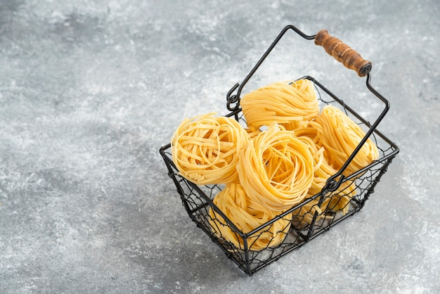 Uncooked noodle rolls in a metallic tray.
