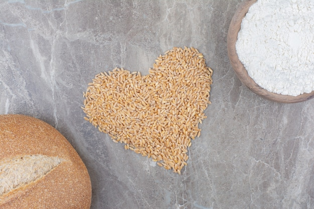 Chicchi di avena crudi con pagnotta di pane sulla superficie di marmo