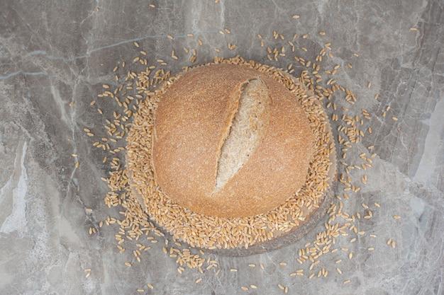 大理石の表面に一斤のパンが付いた未調理のオーツ麦粒