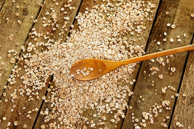 Uncooked oatmeal and wooden spoon