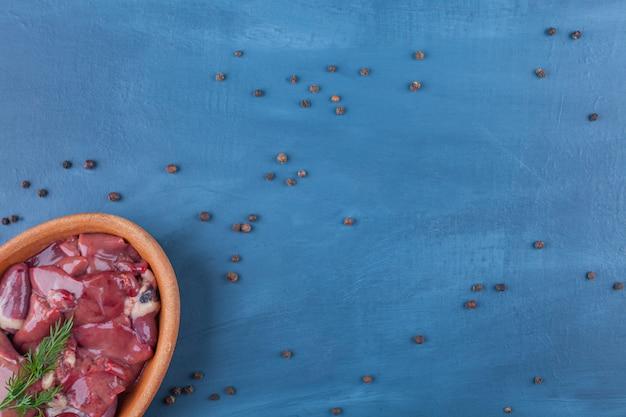 青いテーブルの上にあるボウルの中の未調理の内臓。