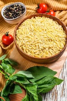 未調理のオルゾペースト。バジルの葉、トマト、ニンニクを使ったリゾーニのレシピ。白色の背景。上面図。