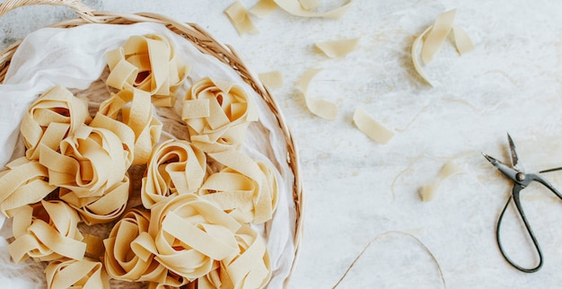 Uncooked pappardelle pasta on a wooden basket