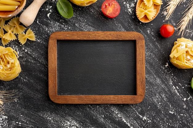 Uncooked pasta arrangement frame on black background with wooden frame