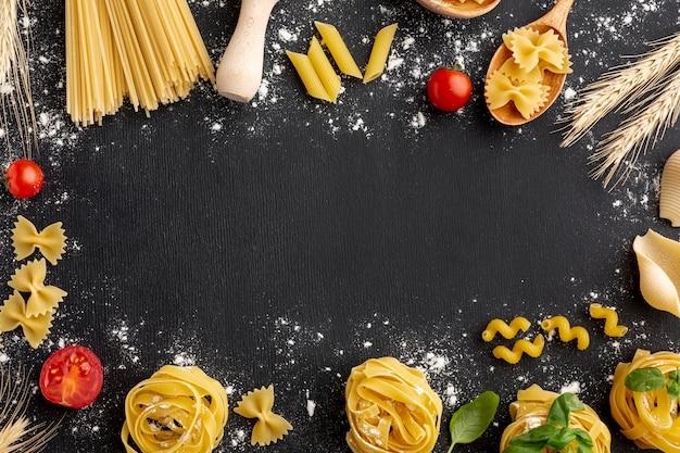 Uncooked pasta arrangement frame on black background