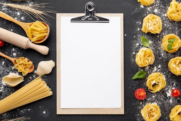 Uncooked pasta assortment with flour on black background with clipboard mock-up