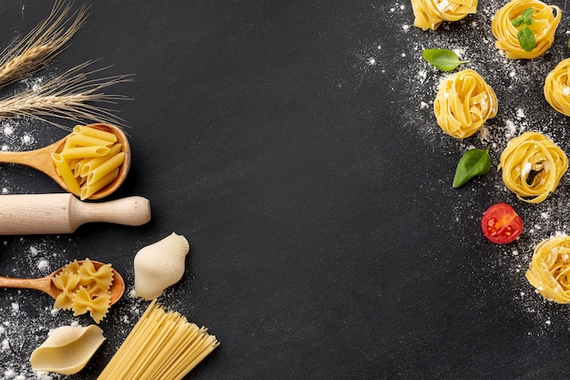 Uncooked pasta assortment with flour and rolling pin on black background
