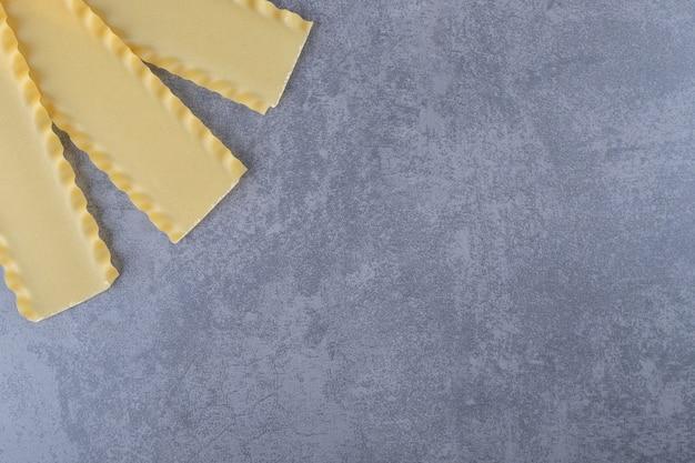 Pasta cruda per cuocere le lasagne su fondo di pietra.