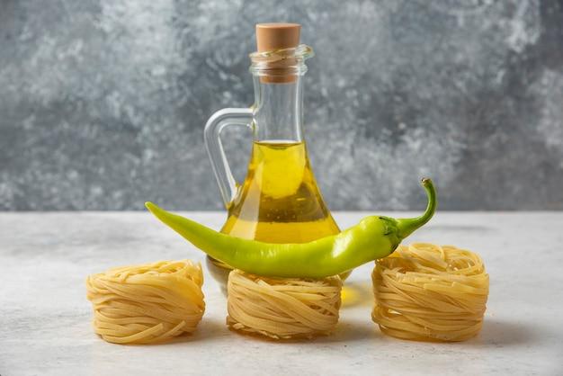 Сырые гнезда макаронных изделий, бутылка оливкового масла и зеленого перца на белом столе.