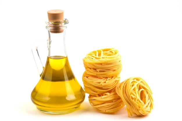 Nidi di pasta cruda e bottiglia di olio su bianco.