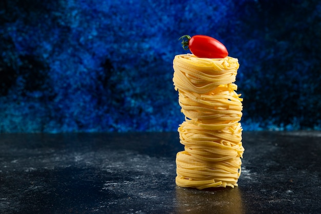 Nidi di pasta cruda e pomodoro sulla tavola di marmo.