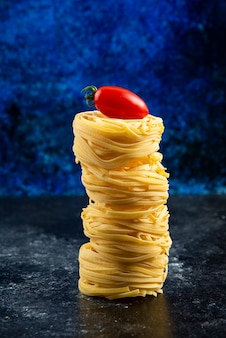 Uncooked pasta nests and tomato on marble table.