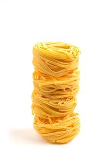 Nidi di pasta cruda su bianco.