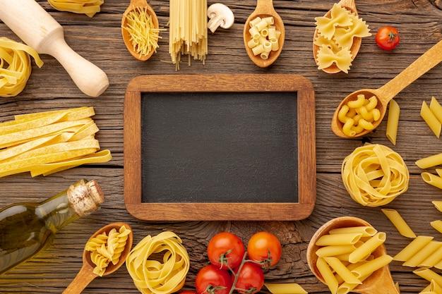 調理されていないパスタオリーブオイルとトマトと黒板のモックアップ