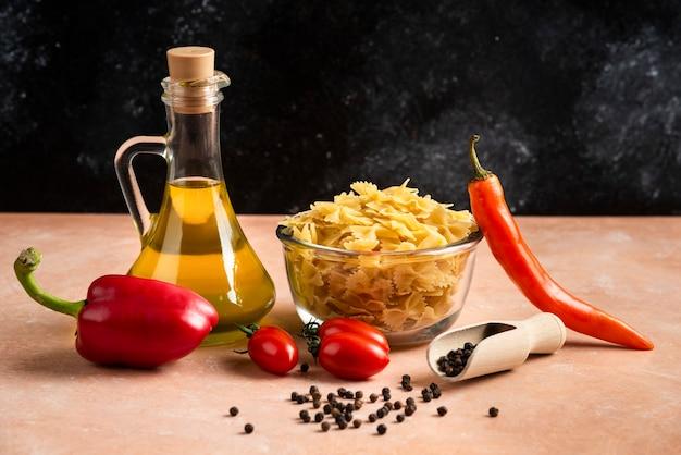 Pasta cruda, verdure e una bottiglia di olio sulla tavola arancione.