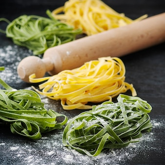 Uncooked pasta with wooden rolling pin