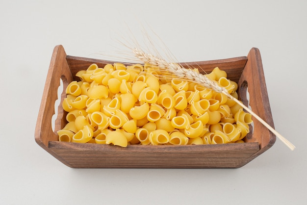 Uncooked pasta on wooden plate with colorful ear of wheat