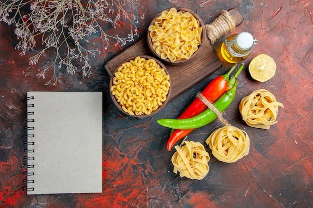Сырые пасты кайенский перец, связанные друг с другом веревкой, масло, бутылка, лимон, чеснок, и блокнот, на столе смешанных цветов