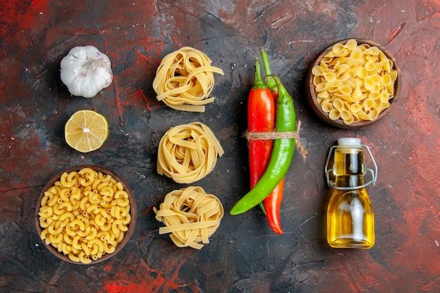 Сырые пасты кайенский перец, связанные друг с другом веревкой, масло, бутылка, лимон, чеснок, на столе смешанных цветов