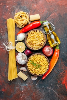 Uncooked pastas oil bottle and foods for dinner preparation on mixed color table