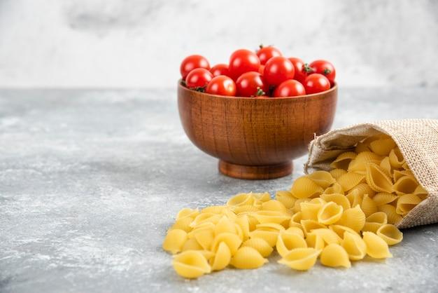 Pasta cruda in un sacchetto rustico con pomodorini sul tavolo di marmo.