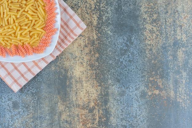 Сырые макароны пенне и фузилли в миске на полотенце на мраморной поверхности.