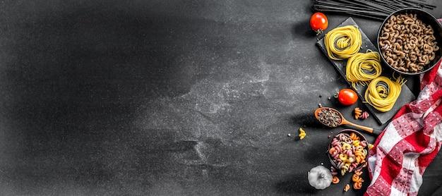 未調理のパイプリゲート、色とりどりのインサラトンド、パスタの巣、スパイスとトマトの灰色のスレート調理の背景、上面図