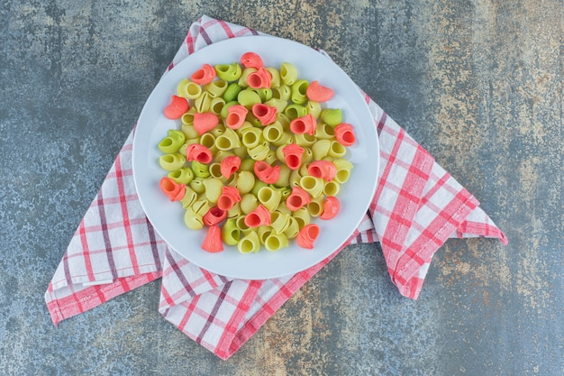 Сырые макароны pipe rigate в тарелке на кухонном полотенце на мраморной поверхности.
