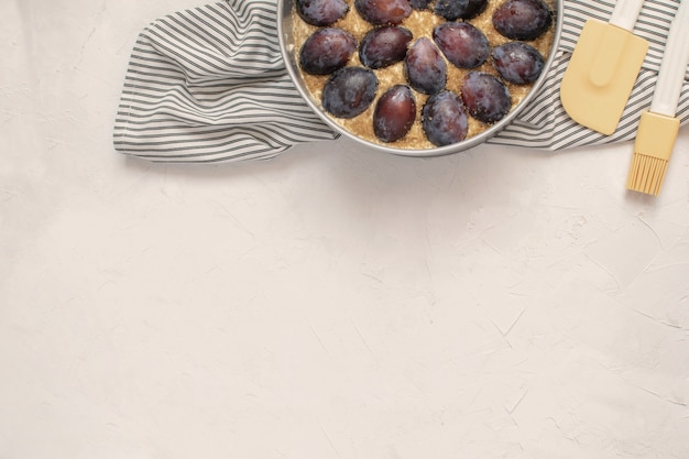 Uncooked plum pie in metal mold, silicone spatula, basting brush